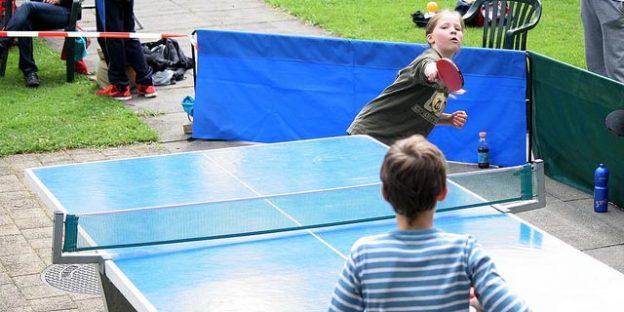 Niños jugando al ping pong en el jardín
