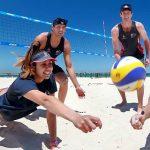 lanzados a rematar el balón en la playa