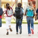 Niños corriendo hacia el colegio