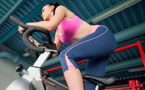chica entrenando con la bicicleta ciclo indoor